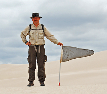 Image of Craig Brabant, standing in a large area of open sand, holding a aerial insect net.